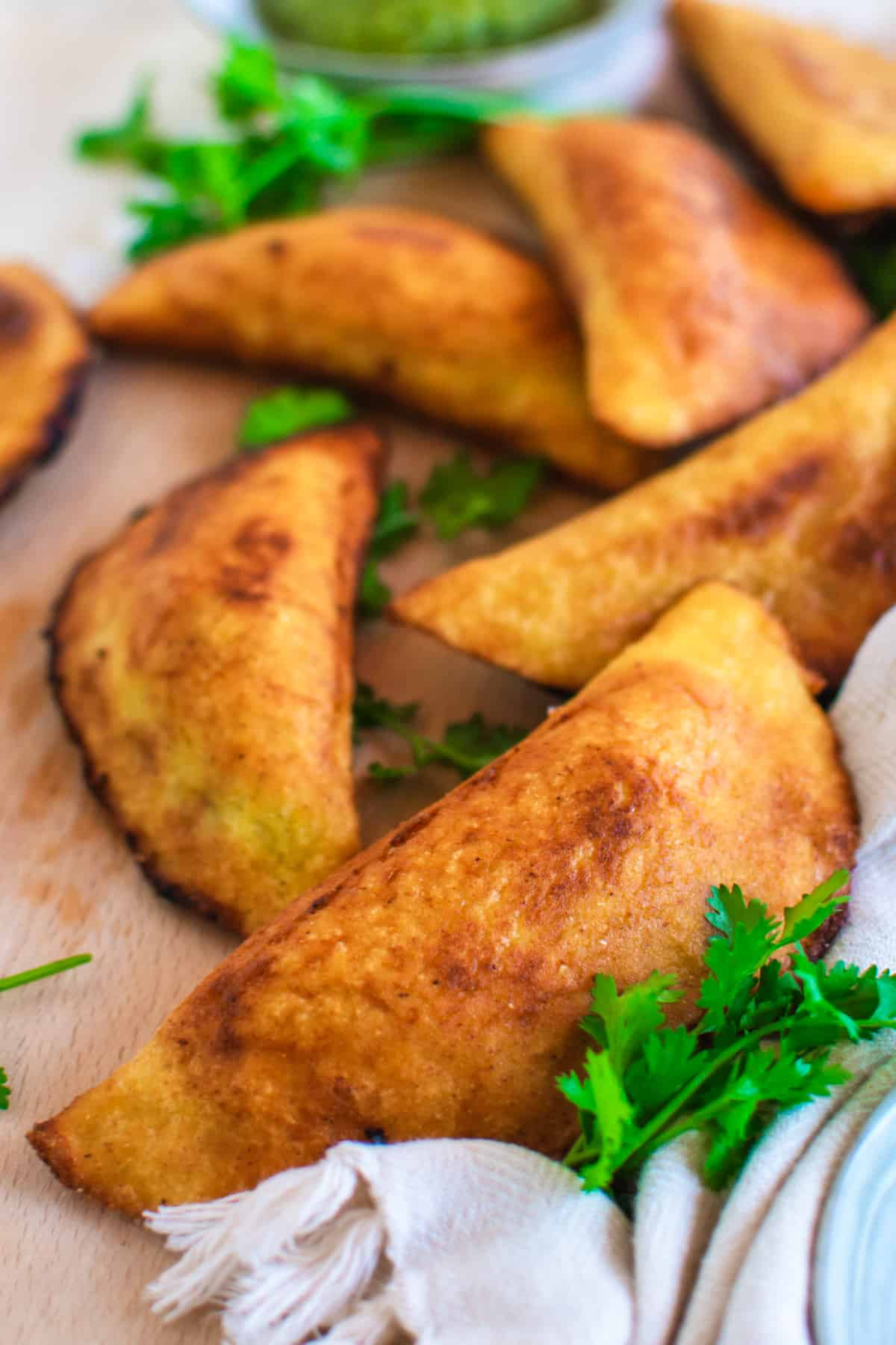 A close up of a Venezuelan empanada garnished with coriander.