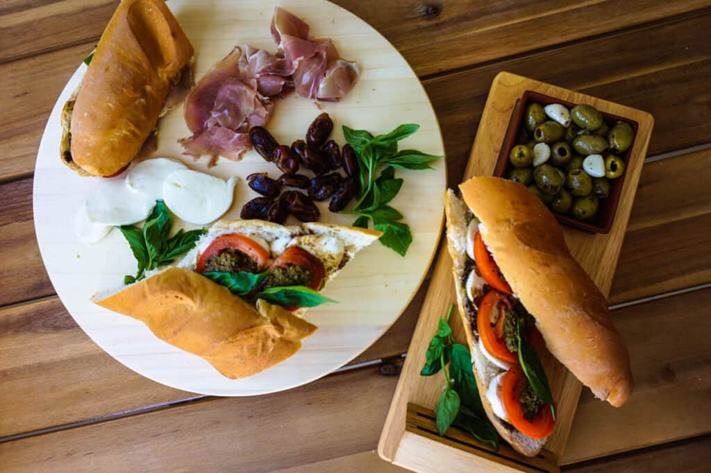 An italian lunch platter with two baguettes and olives.