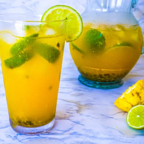 A glass and pitcher of passionfruit lemonade garnished with lime slices.