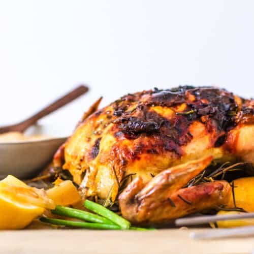 A close up of the roast chicken with veggies on the side of it.