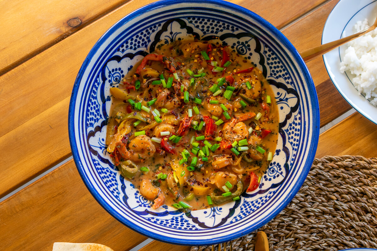 The delicious shrimp curry in a Arabic-style bowl with side dishes