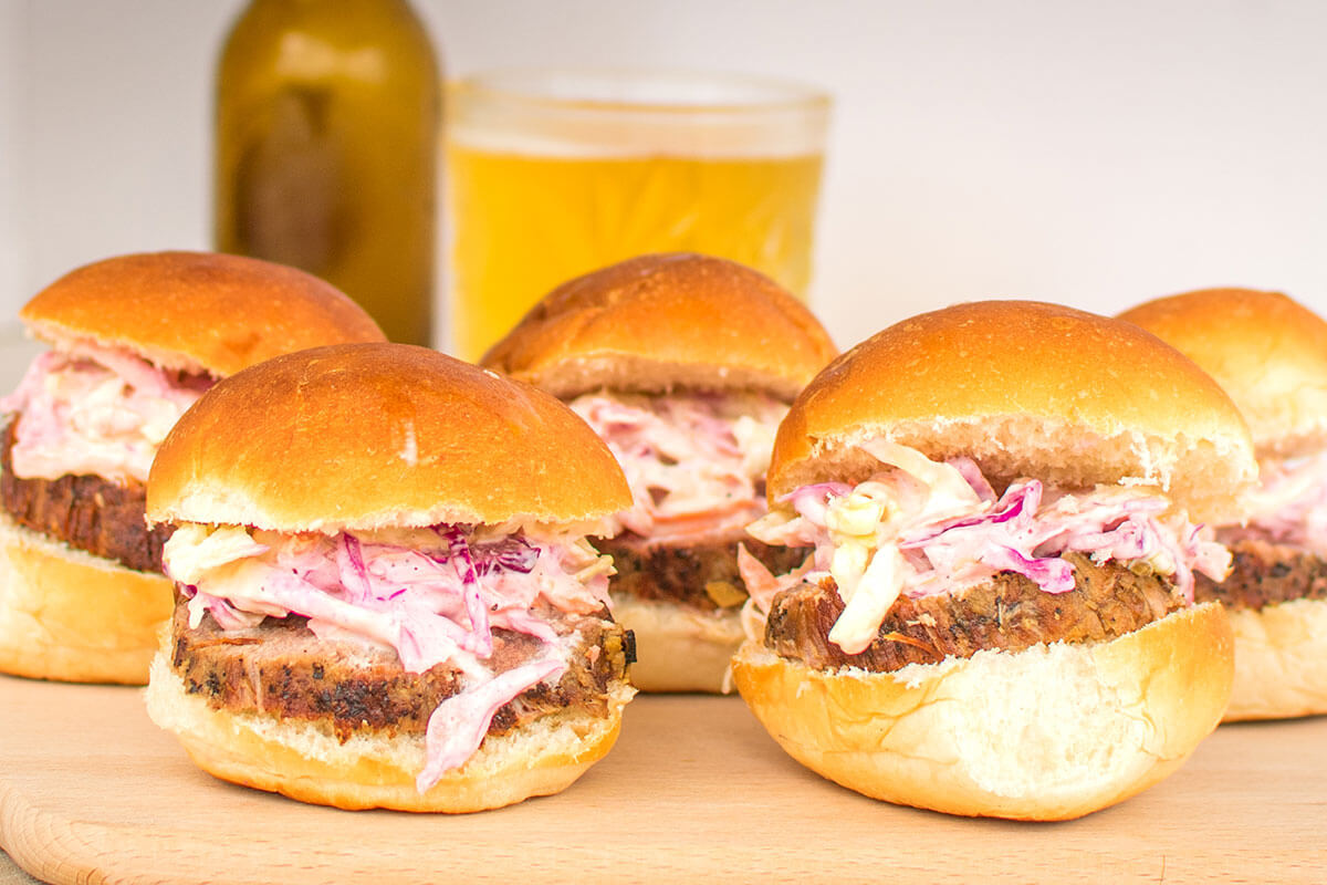 A couple of roast beef slider with a glass of beer