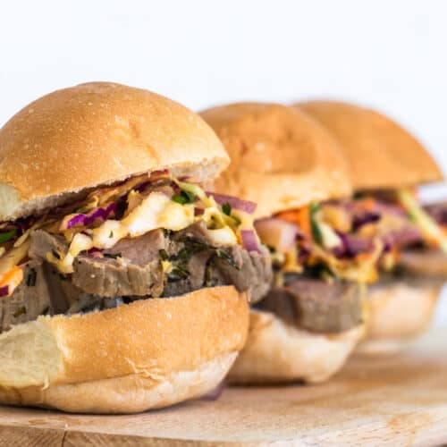 3 roast beef sliders with Caribbean slaw on a serving wooden tray.