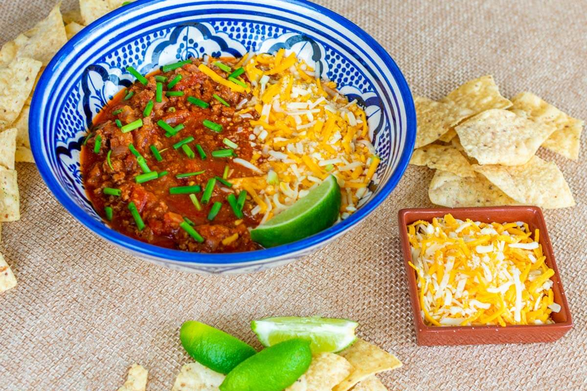 A bowl of chili con carne dip with cheese and nacho on the side.