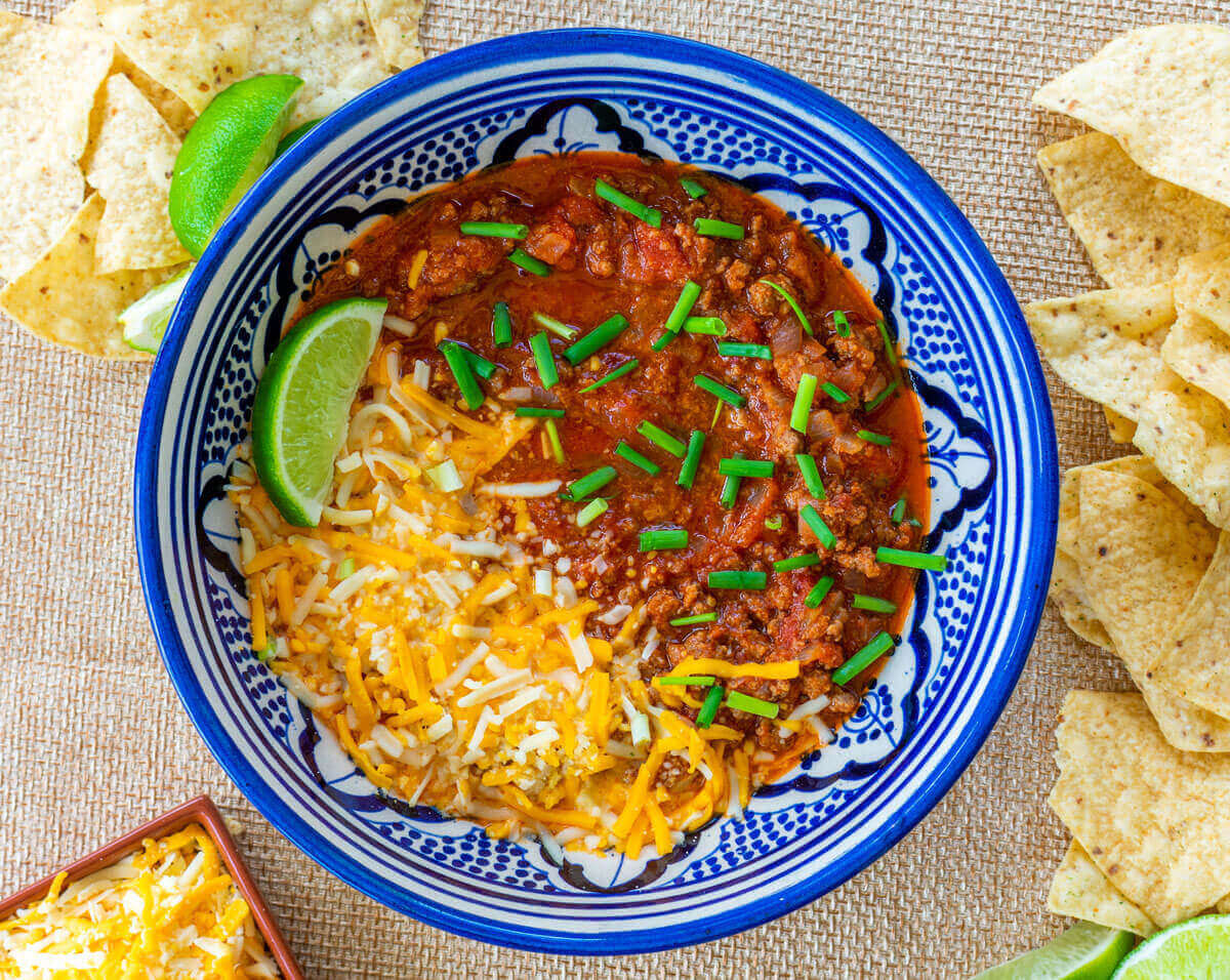 Chili con carne dip in a bowl with nachos on the side and cheese
