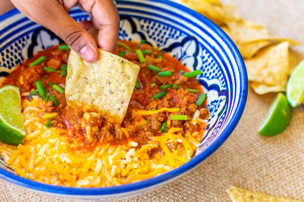 A nacho dipped in a bowl with the chili con carne dip.