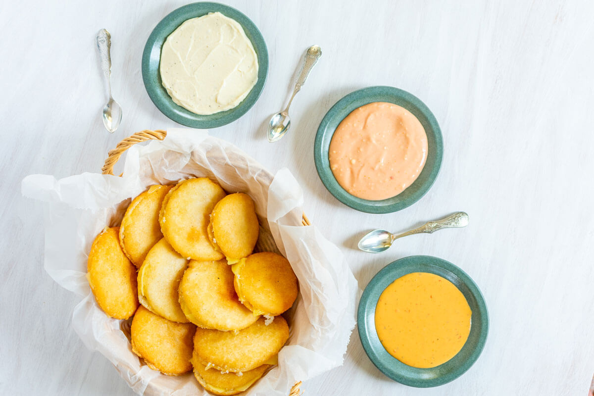 A basket with mini arepas with cheese and 3 different sauces.