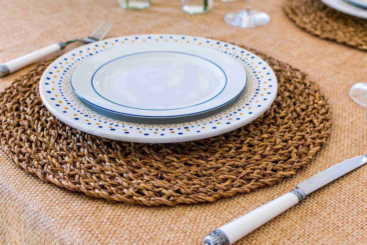 A close-up shot of a tablescape with two design plates and placemat.