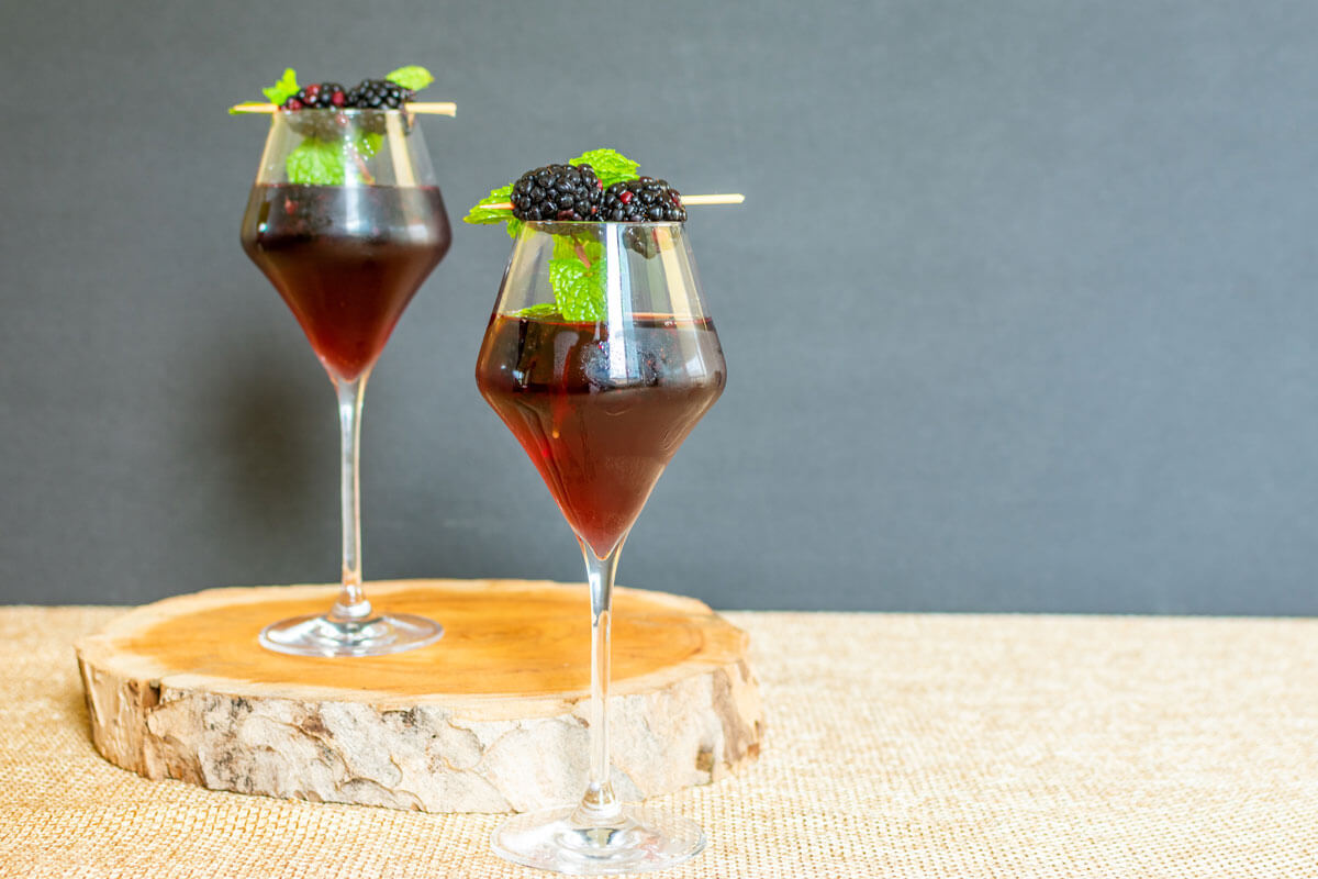 A glass with The Raven cocktail recipe and fresh blackberries and mint as garnish.