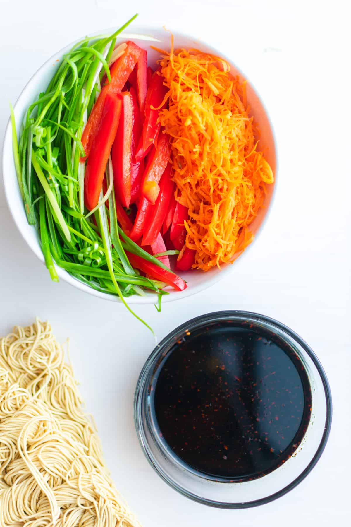A bowl of shredded carrots, sliced paprika, and sliced green onion. A bowl of Kung Pao Noodles sauce and some raw noodles on the side.