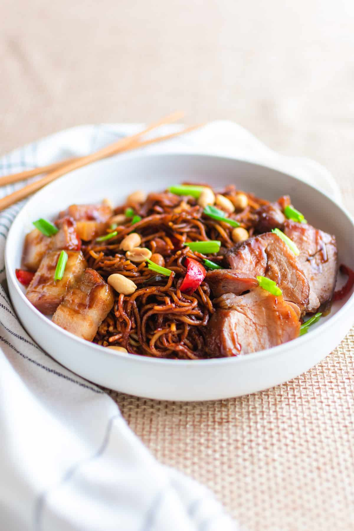 A shallow white bowl iwth kung pao noodles and char siu pork