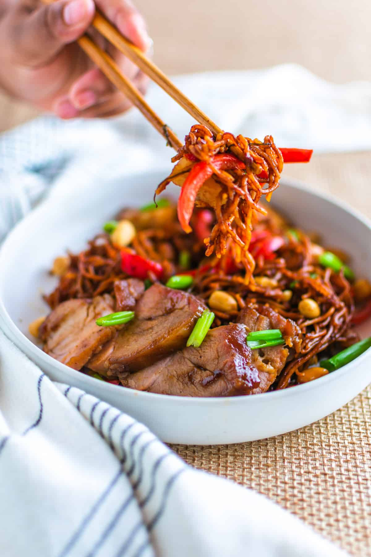 A shallow white bowl iwth kung pao noodles and char siu pork being picked up with a chopsticks.