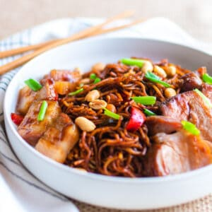 A shallow white bowl iwth kung pao noodles and char siu pork.