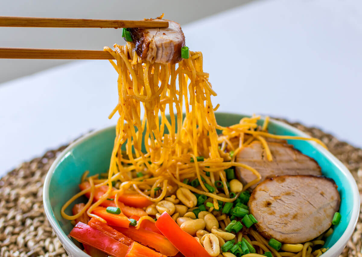 Bowl with noodles, chopsticks, vegetables, garnished with peanuts and char siu.