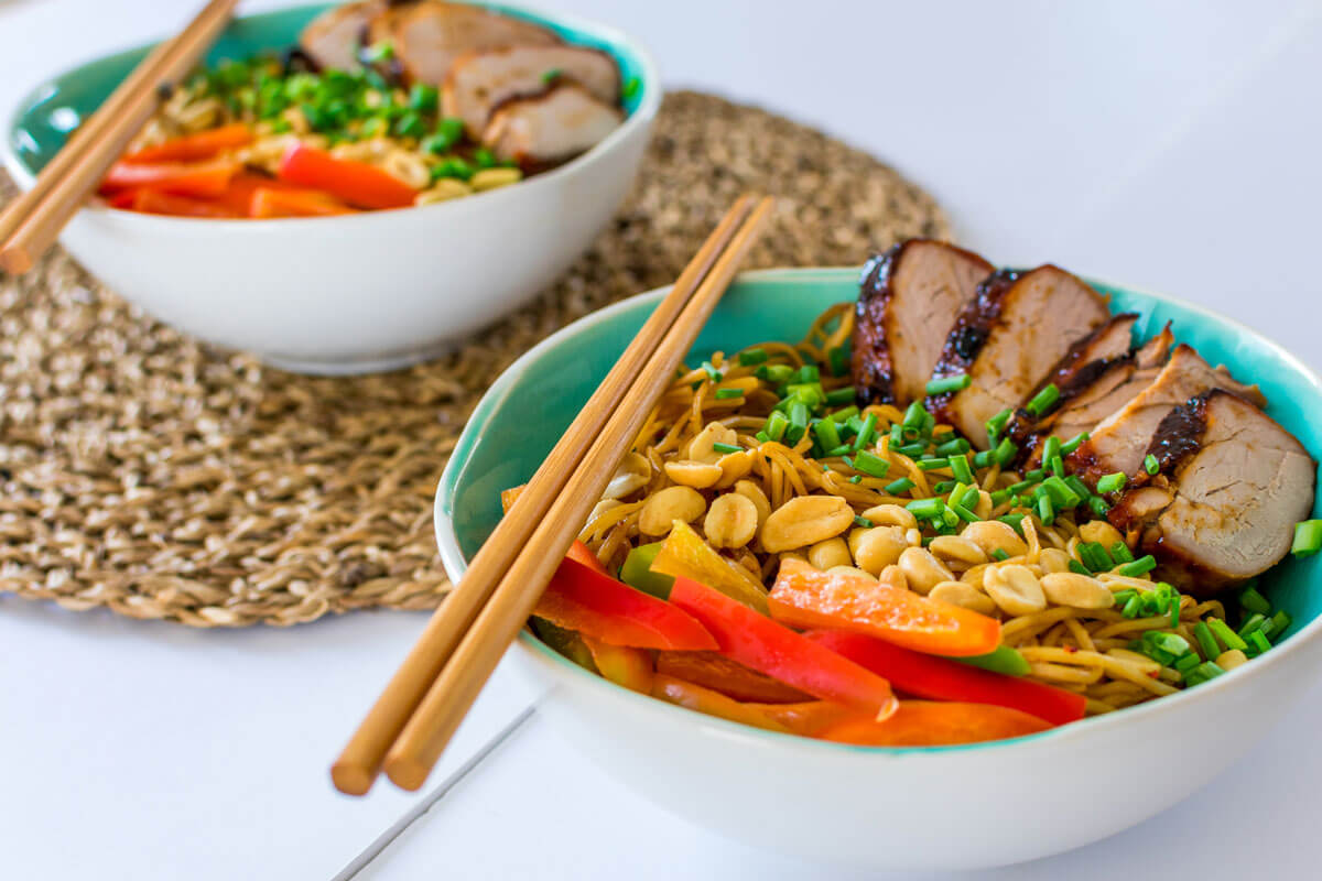 Bowls with noodles, chopsticks on top of the bowl, vegetables, garnished with peanuts and char siu.