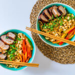 Flat lay of bowls with noodles, chopsticks on top of the bowl, vegetables, garnished with peanuts and char siu.