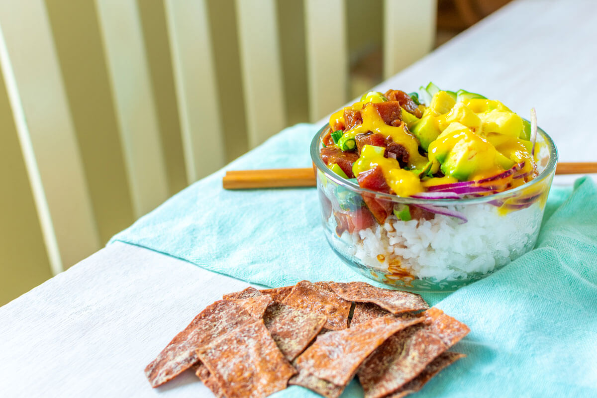 A tuna poké bowl with wonton chips on a blue kitchen towels with chopsticks and a chair in the background.