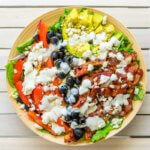 A flay lay of of the BLT salad with ranch dressing on a tabletop.