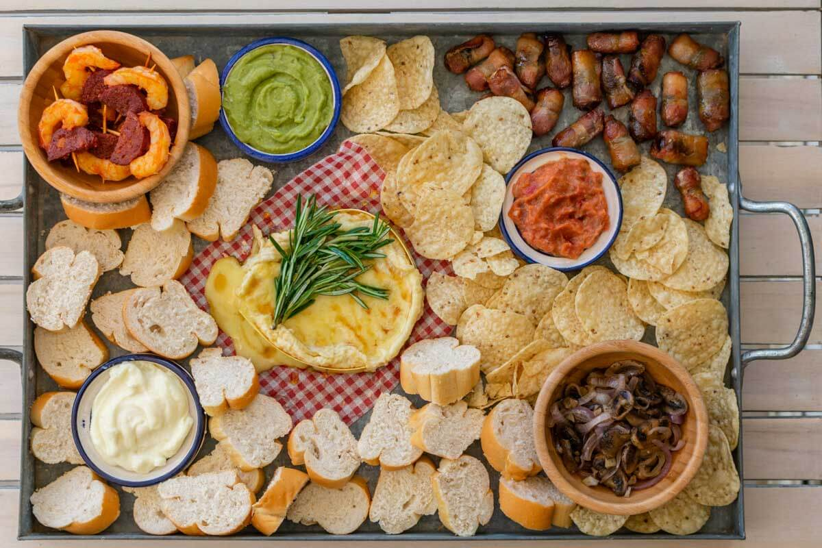 An overhead shot of the christmas appetizer platter with Camembert, bacon-wrapped dates, shrimps-chorizo pinchos, dips, bread, and chips.