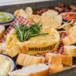 The center part of the Christmas appetizer platter with the Camemert garnished with rosemary, and the chips and bread around it.