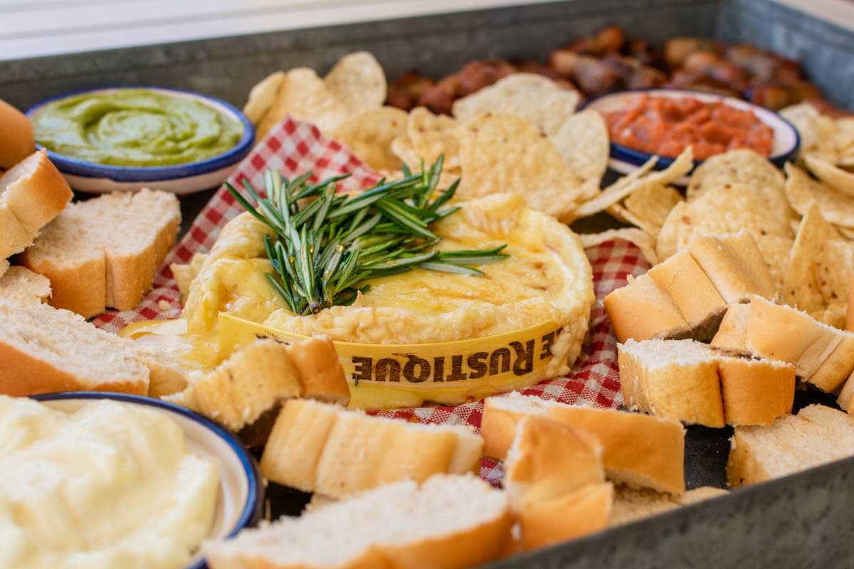 The center part of the Christmas appetizer platter with the Camembert garnished with rosemary, and the chips and bread around it.
