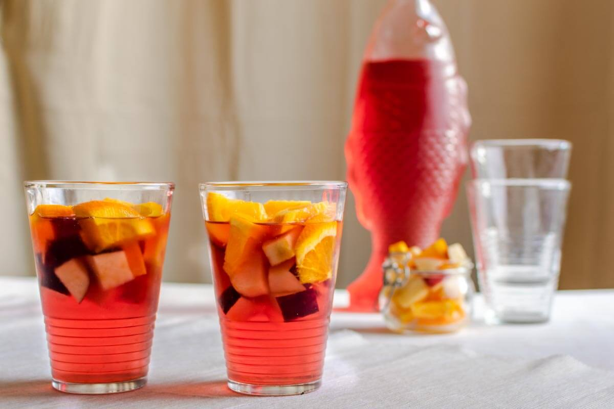 2 glasses and a pitcher of ginger-cranberry mocktail with two empty glasses next to the pitcher and a mason jar with fruits.