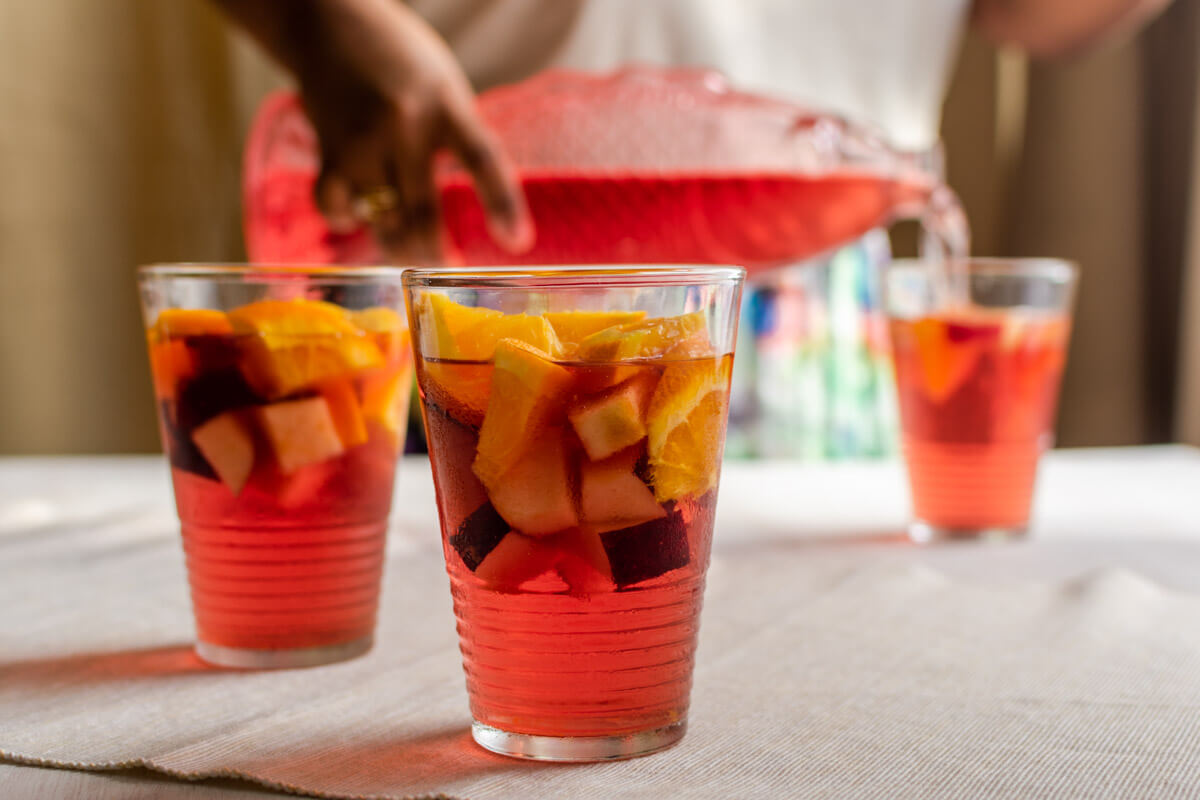 2 glasses of ginger-cranberry mocktail filled with fruits and in the back someone pouring the mocktail in a glass.