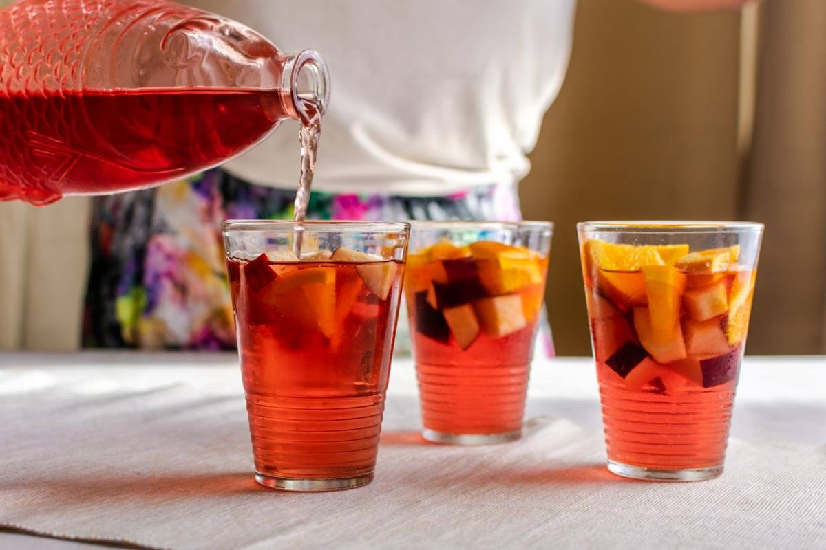 2 glasses of ginger-cranberry mocktail and a women pouring the mocktail in one of the front glasses.