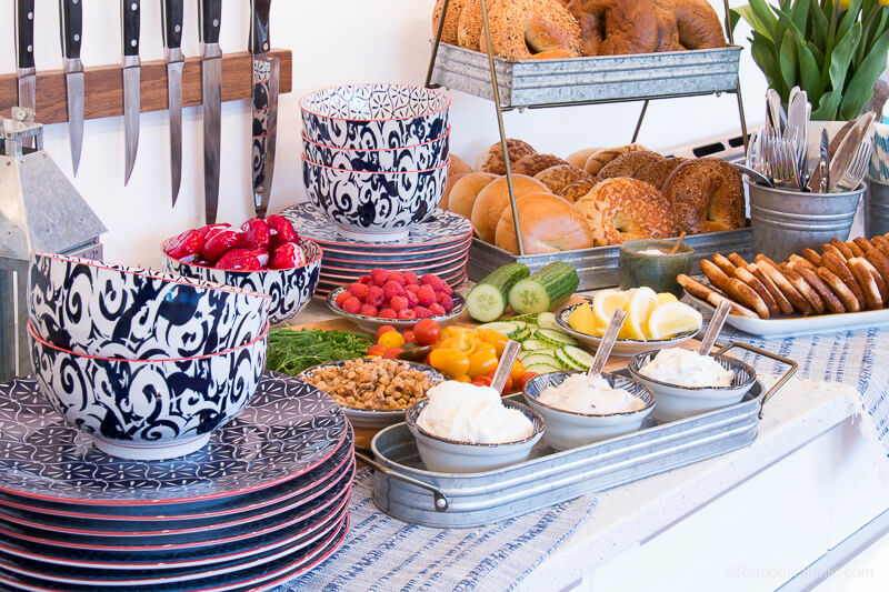 Bagels brunch bar with plates, different spreads, bagels, and fruits and vegetables.