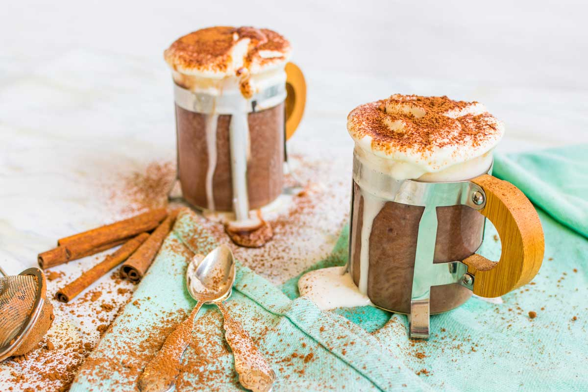 Front view of two cups of rooibos hot chocolate with whipped cream and cocoa powder.