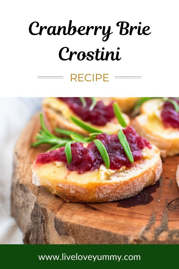 A cranberry brie crostini garnished with rosemary on a wooden serving plate