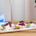 Baked cranberry brie crostini on a wooden board with a blue kitchen towel and green leaves in the background.