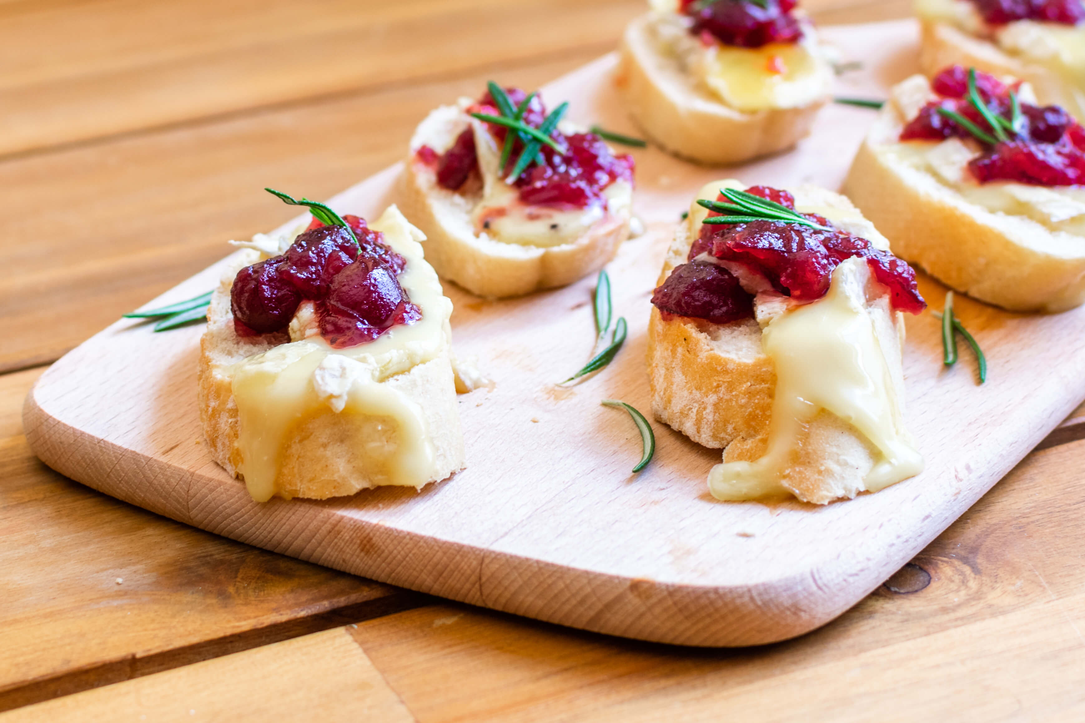 Baked cranberry brie crostini on a wooden board and garnished with rosemary sprigs.