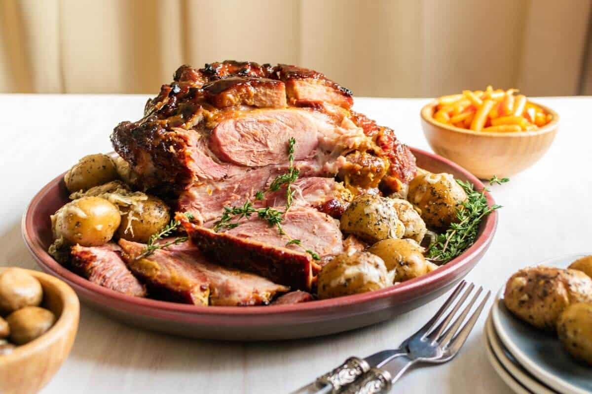 A full baked ham with ham sliced, garnished with thyme sprigs, and roasted carrots, potatoes, and mushrooms as side dish.