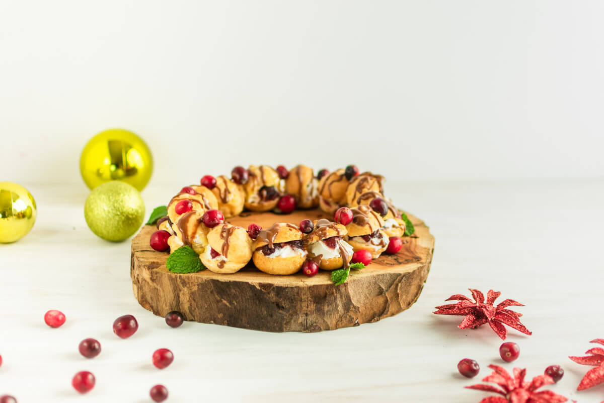An angled view of a profiteroles wreath with drizzled chocolate, garnished with cranberries and mint, and styled with Christmas decorations.