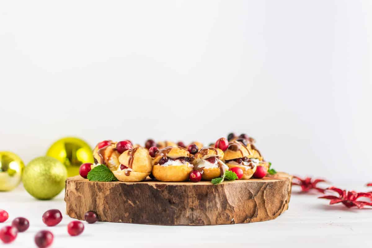 A front view of a profiteroles wreath with drizzled chocolate, garnished with cranberries and mint, and styled with Christmas decorations.