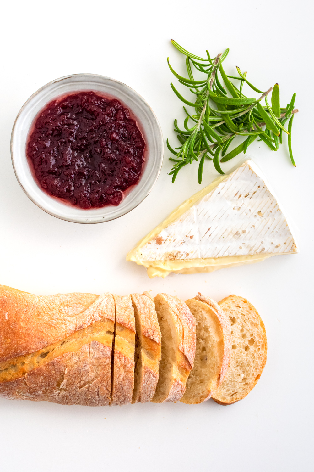 A ciabatta, brie, rosemary leaves, and a cranberry sauce in a pinch bowl.