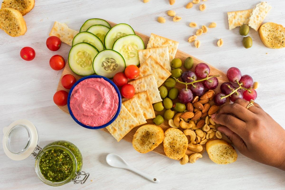 An overhead shot of a healthy vegan appetizer board with nuts, bread and kale pesto on the side plus a hand grabbing some food.