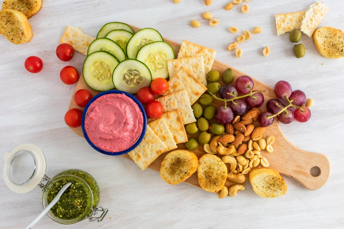 An overhead shot of a healthy vegan appetizer board with nuts, bread and kale pesto on the side.