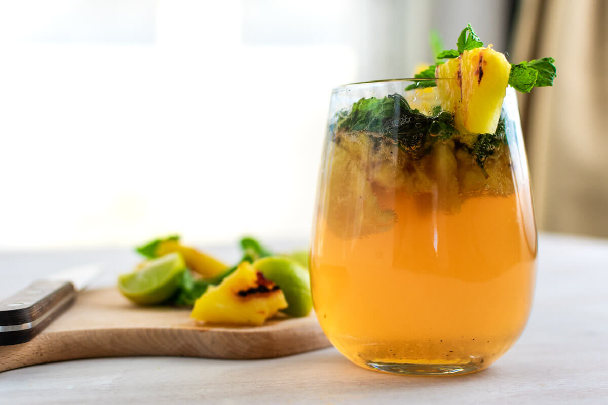 A glass of charred pineapple mojito placed on and in front of a wooden board with pineapple chunks, limes, and a knife on it.