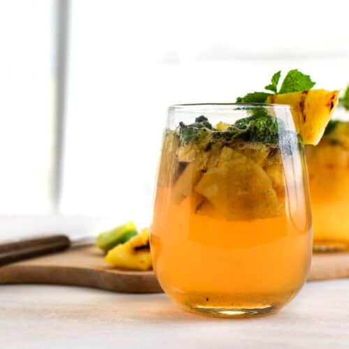 2 glasses of charred pineapple mojito placed on and in front of a wooden board with pineapple chunks, limes, and a knife on it.