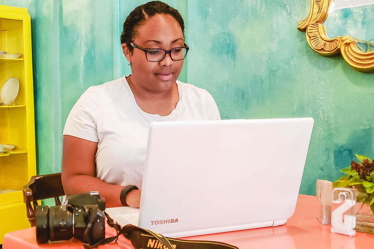 Picture of the blogger behind Live Love Yummy, sitting at a table with a white laptop in front of her and a Nikon camera. The wall is blue-green.