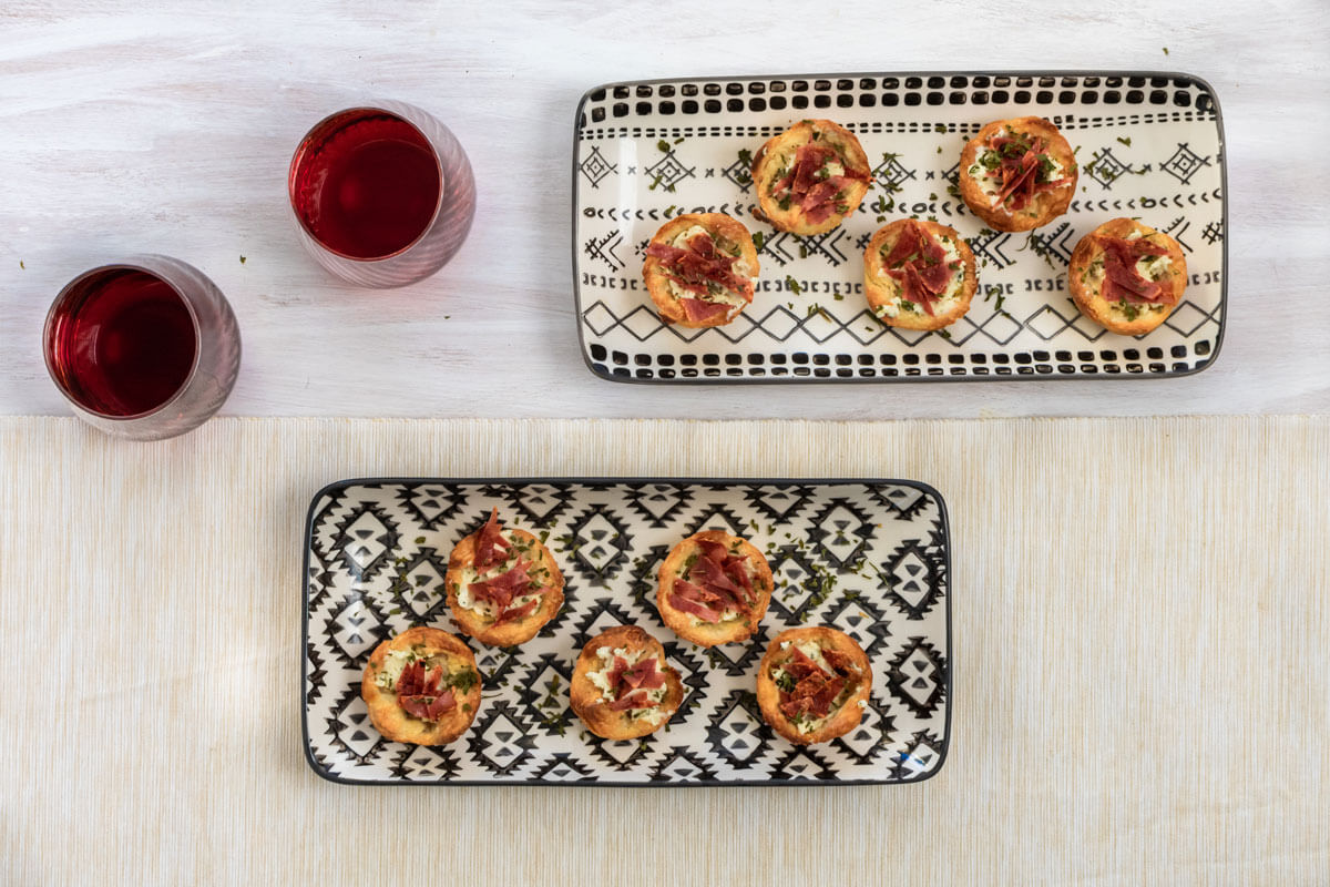 Turkey bacon & boursin puffs spread on two black and white serving tray with two wine glasses on the side.