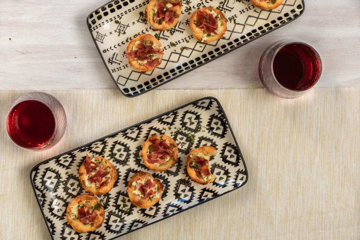 Turkey bacon & boursin puffs spread on two black and white serving tray, placed diagonally, with two wine glasses on the side.
