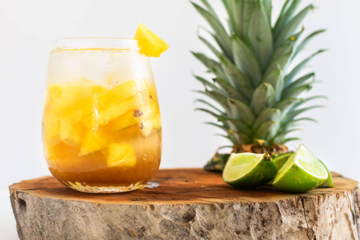 Pineapple and Tamarind Agua Fresca on a wood trunk with a pineapple crown and lime wedges on the side.