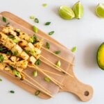 An overhead view of a wooden board with tofu skewers, garnished with spring onions, and half of an open avocado with lime quarters on the side.