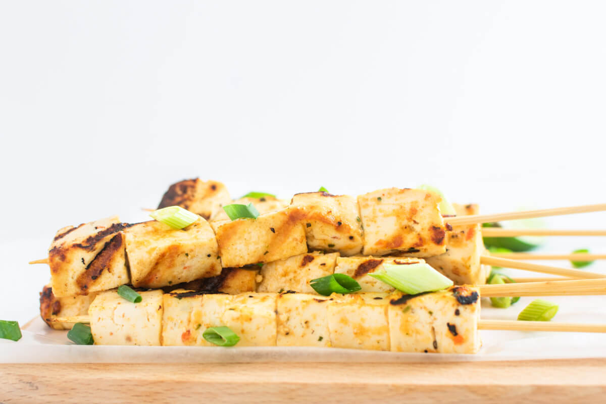 Tofu skewers on a wooden board garnished with spring onions.