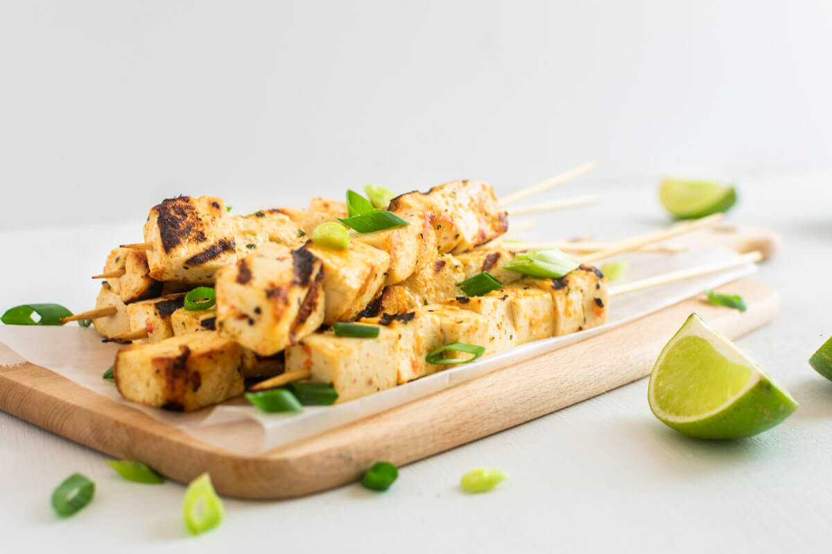 Tofu Tofu skewers on a wooden board garnished with spring onions and lime quarters on the side.