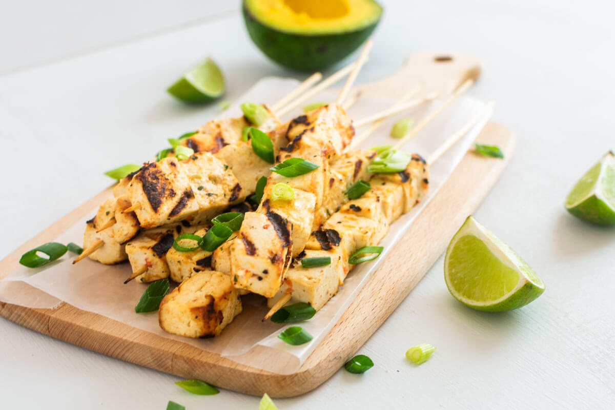 A angled-view of a wooden board with tofu skewers, garnished with spring onions, and half of an open avocado with lime quarters on the side.