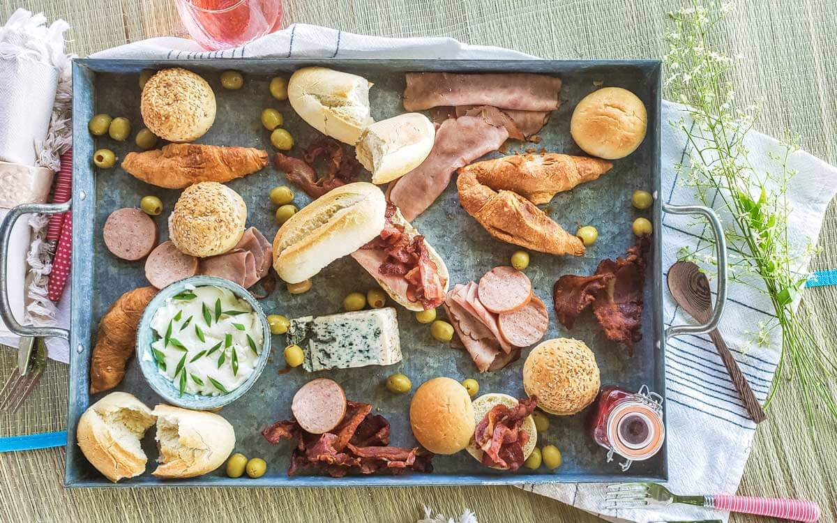 A grey metal tray on top of white and black linnen with assorted bread, meat, spread and cheese.